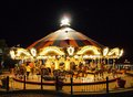 Merry-go-round in an amusement park at night lit up with bright lights Royalty Free Stock Photo