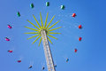 Merry go round chain swing carousel ride in amusement park shot from below blue sky Royalty Free Stock Photo