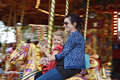 Merry go round fun young child and mother enjoying a traditional Stock Image