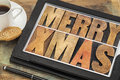 Merry xmas on digital tablet in letterpress wood type computer with stylus pen coffee cup and cookie Stock Photos