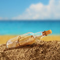 Message in the bottle on seashore beach sand Stock Image