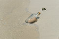 Message in a bottle washed ashore on tropical beach Royalty Free Stock Photo