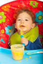 Messy baby eating puree with spoon by yourself and sitting chair Royalty Free Stock Images