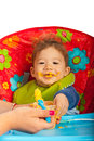 Messy baby with puree boy eating and sitting in chair Royalty Free Stock Photography