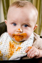 Messy baby wearing bib after eating solid food Royalty Free Stock Photo