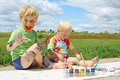 Messy children painting two happy young a little boy and his baby brother are sitting outside on a summer day a picture and Royalty Free Stock Images