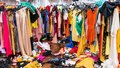 Messy clearance section in a clothing store, with colorful garments on racks and on the floor Royalty Free Stock Photo