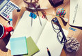 Messy designer s table with blank note and tools Royalty Free Stock Image