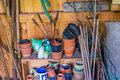 Messy gardening tools in tool shed stacked on shelf Royalty Free Stock Photo