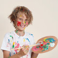 Messy kid with paint pallete Stock Photos