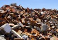 Messy pile of bricks on blue sky jagged red and debris against Stock Photo