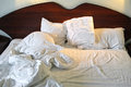 Messy unmade bed wake up hour in the morning in hotel room bedding sheets and pillow Royalty Free Stock Photos