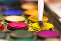 Messy used water color paint box and paint brush closeup of Royalty Free Stock Photos