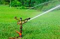 A metal automatic water sprinkler in the field Stock Image