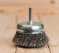 Metal brush on a drill to remove rust on a light wooden background Royalty Free Stock Photo