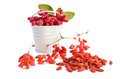 Metal bucket with barberries near heap of goji berries on white background Royalty Free Stock Photography