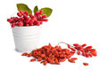 Metal bucket with berberries near heap of goji berries on white background Stock Photo