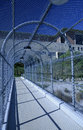 Metal chainlink fence over a walkway curved pedestrian Stock Photos