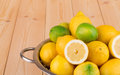Metal colander full of lemons and limes wooden background Royalty Free Stock Photos