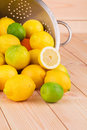 Metal colander full of lemons and limes wooden background Stock Image