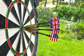 Metal darts have hit the red bullseye on a dart board. Darts Game. Darts arrow in the target center darts in bull`s eye close up. Royalty Free Stock Photo