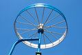 Metal detail as a bicycle wheel painted in the form of on the blue sky background Royalty Free Stock Photo