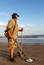 Metal detecting the beach man on Royalty Free Stock Photo