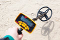Metal detector in action sand background Stock Photography