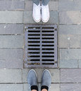 Metal drain and feet on the road around Stock Photo