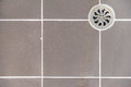 Metal drain hole in the dirty tiled floor a Royalty Free Stock Images