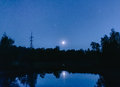 Metal electric poles in the moonlight at the lake Royalty Free Stock Photo