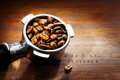 Metal espresso filter with coffee beans Stock Photography