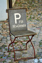 Metal folding chair with parking hint old on natural stone street Stock Image
