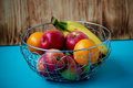 Metal fruit bowl on a wooden surface. Close. Bananas, oranges and apples Royalty Free Stock Photo