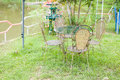 Metal garden chair in the garden on green grass Royalty Free Stock Image