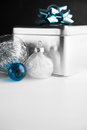 Metal gift box with blue bow and xmas baubles on white and black wooden backgrounds.