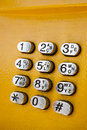 Metal keypad with numbers part of yellow public phone on the street Royalty Free Stock Photography