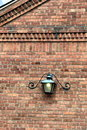 Metal lamp hanging from ornate brick building Royalty Free Stock Photo