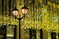 Metal lantern on background of shiny neon garland, as yellowed leaves, vintage tones. Fall, fest backdrop. Festive Royalty Free Stock Photo