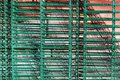 Metal mesh netting chain link green fence work piece stack on building wall background outdoors sunny day Royalty Free Stock Photo