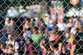 Metal netting and crowd Royalty Free Stock Image