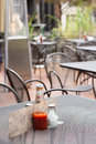 A metal outdoor restaurant table with ketchup bottle salt shaker and menu an heater and other tables are in the Royalty Free Stock Images