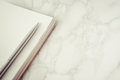 Metal pen on a blank notebook page with marble Royalty Free Stock Photo