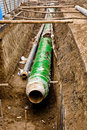 Metal pipes lieing in the trench. Royalty Free Stock Photography