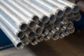 Metal pipes threaded on shelf Stock Image
