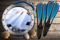 Metal porthole with sea abyss landscape blue on wooden floor sand seashells blue flippers and blue snorkel diving Stock Photography