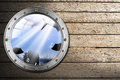 Metal porthole with sea abyss landscape metallic bolts and blue on wooden floor sand Stock Images