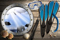 Metal porthole with sea abyss landscape on wooden floor sand seashells flippers snorkel and mask for diving and spear gun Royalty Free Stock Images
