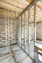 Metal profile frame for plasterboard walls and pipes with valves of a heating system in the house. Royalty Free Stock Photo