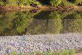 Metal protective mesh near the canal with water protects the shedding of gravel roads stones mound Royalty Free Stock Photo